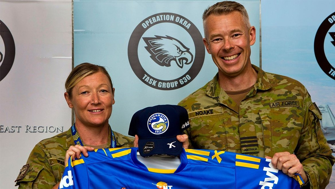 Commanding Officer Combat Support Unit 15, Wing Commander Peter Noake (right), presents Leading Aircraftwoman Kerry Paszyn with the Paramatta Eels jersey and hat gifted to her by the Paramatta Eels Rugby League Club.